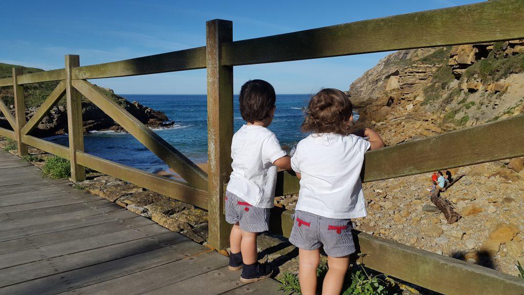 nietos de abuela a la ultima en la playa mirando el mar