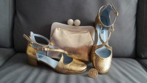 zapatos comodos dorados, bolso de mano y anillo dorado