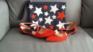 zapatos rojos planos y bolso de manocon estrellas