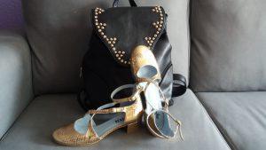 zapatos dorados y mochila negra con tachuelas doradas
