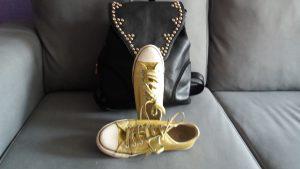 deportivas converse doradas con mochila negra de tachuelas