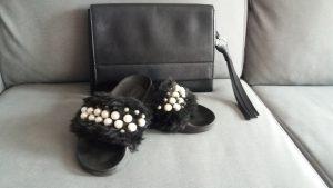 chanclas negras con pelo y perlas blancas y bolso negro de mano