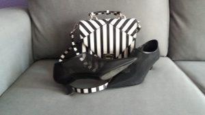 zapatos negros con tacón medio y bolso de rayas blanco y negro pequeño