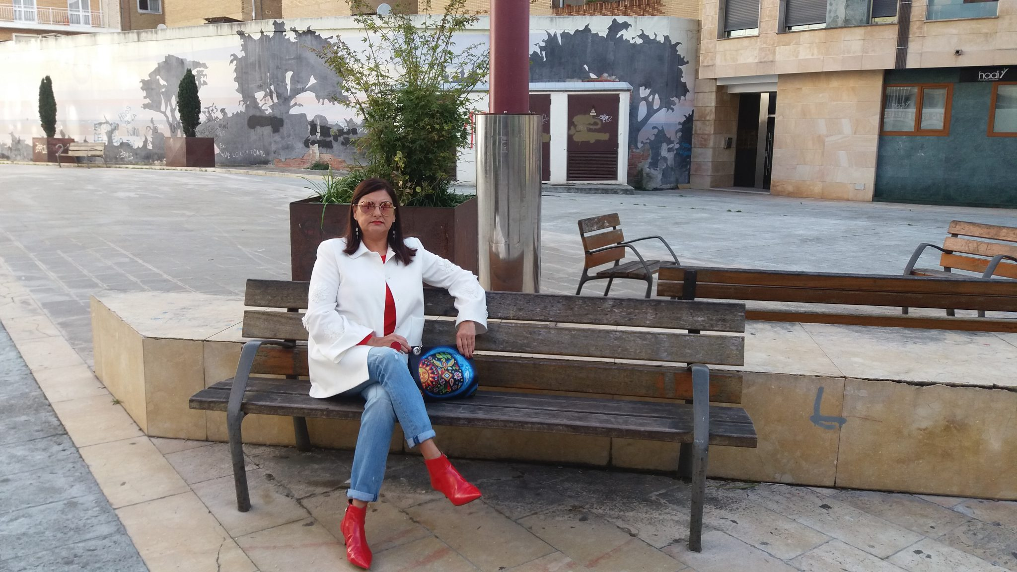 La abuela Maribel sentada en un banco con vaqueros y botines rojos