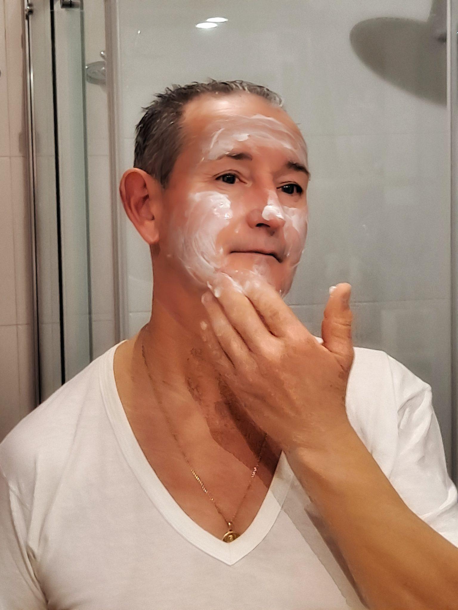 el marido de abuela a la última se aplica crema en la cara frente al espejo.
