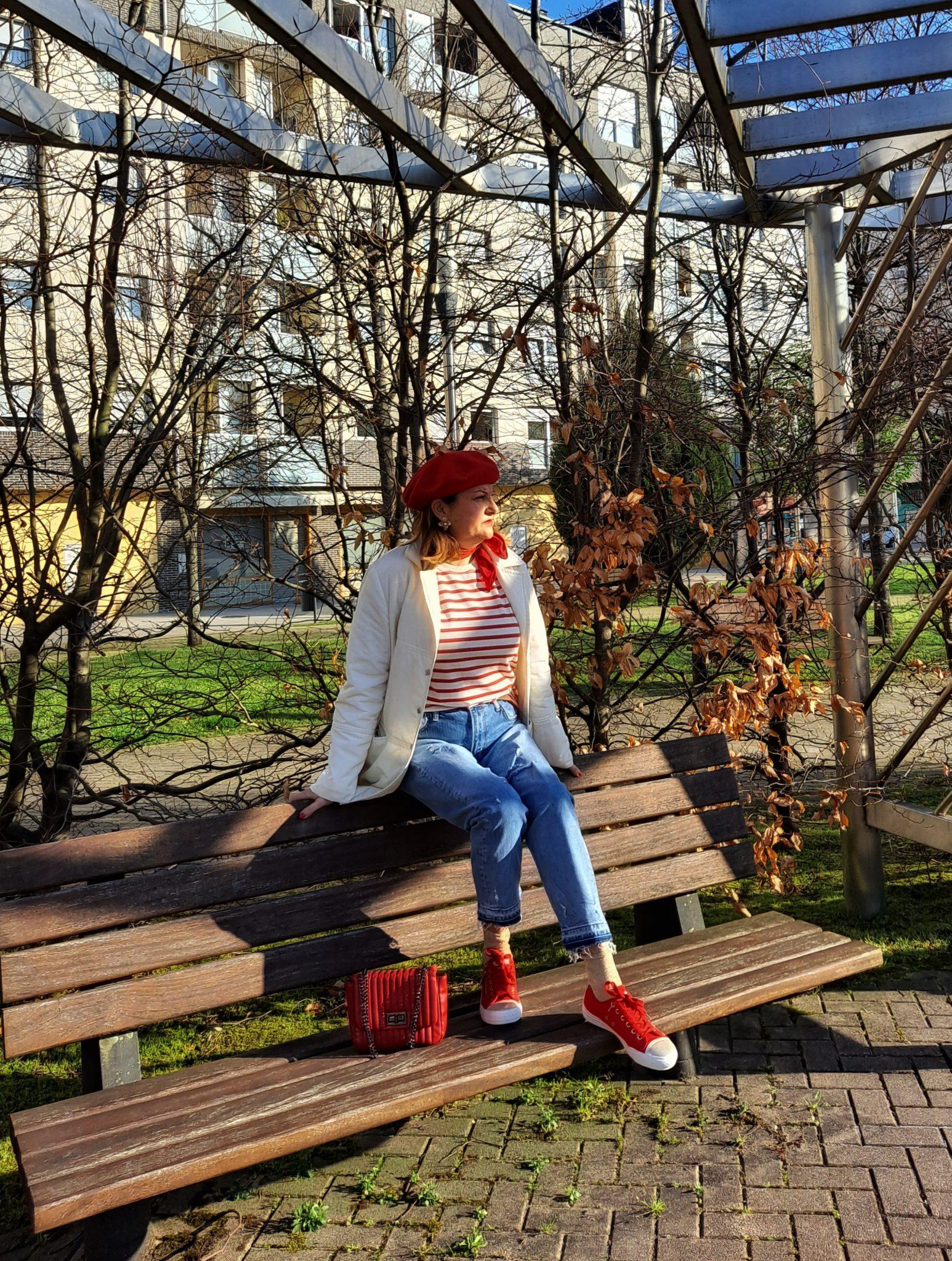 abuela a la ultima sentada en un banco con su boina roja y jersey de rayas