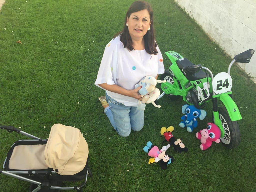 abuela Maribel jugando en el cesped con los juguetes de sus nietos
