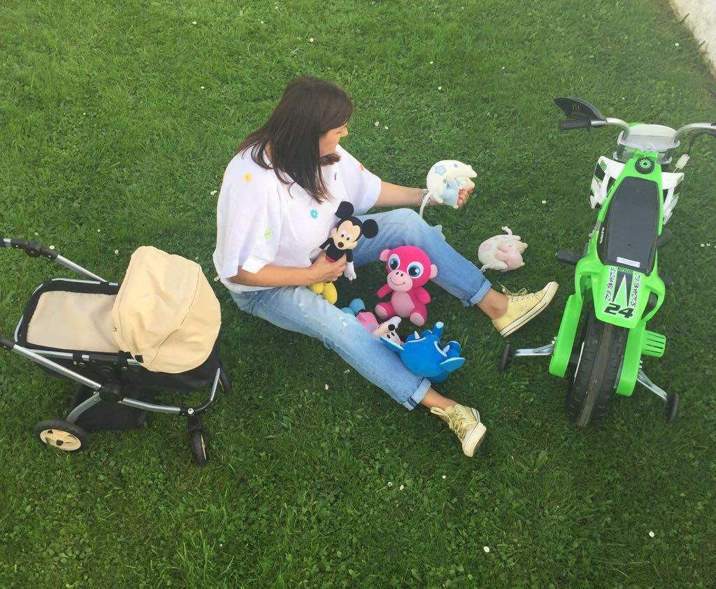 Abuela sentada en el cesped con juguetes de sus nietos