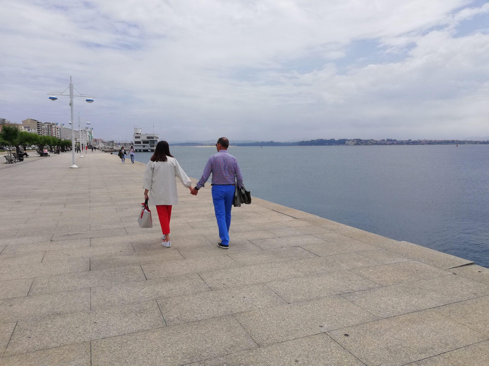 abuela a la ultima y abuelo de paseo cojidos de la mano al borde del mar