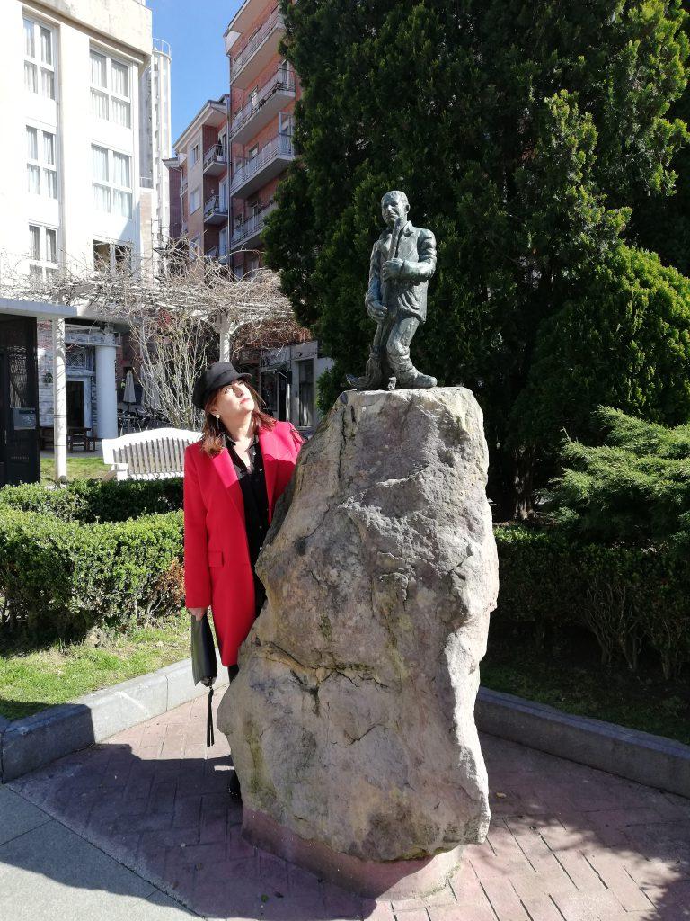 abuela a la ultima posa al lado de la estatua de mero el barrendero