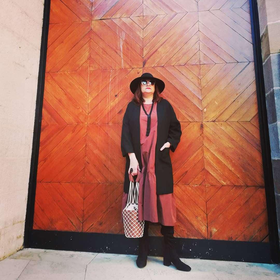 abuela a la ultima posando para foto en una puerta grande de su ciudad