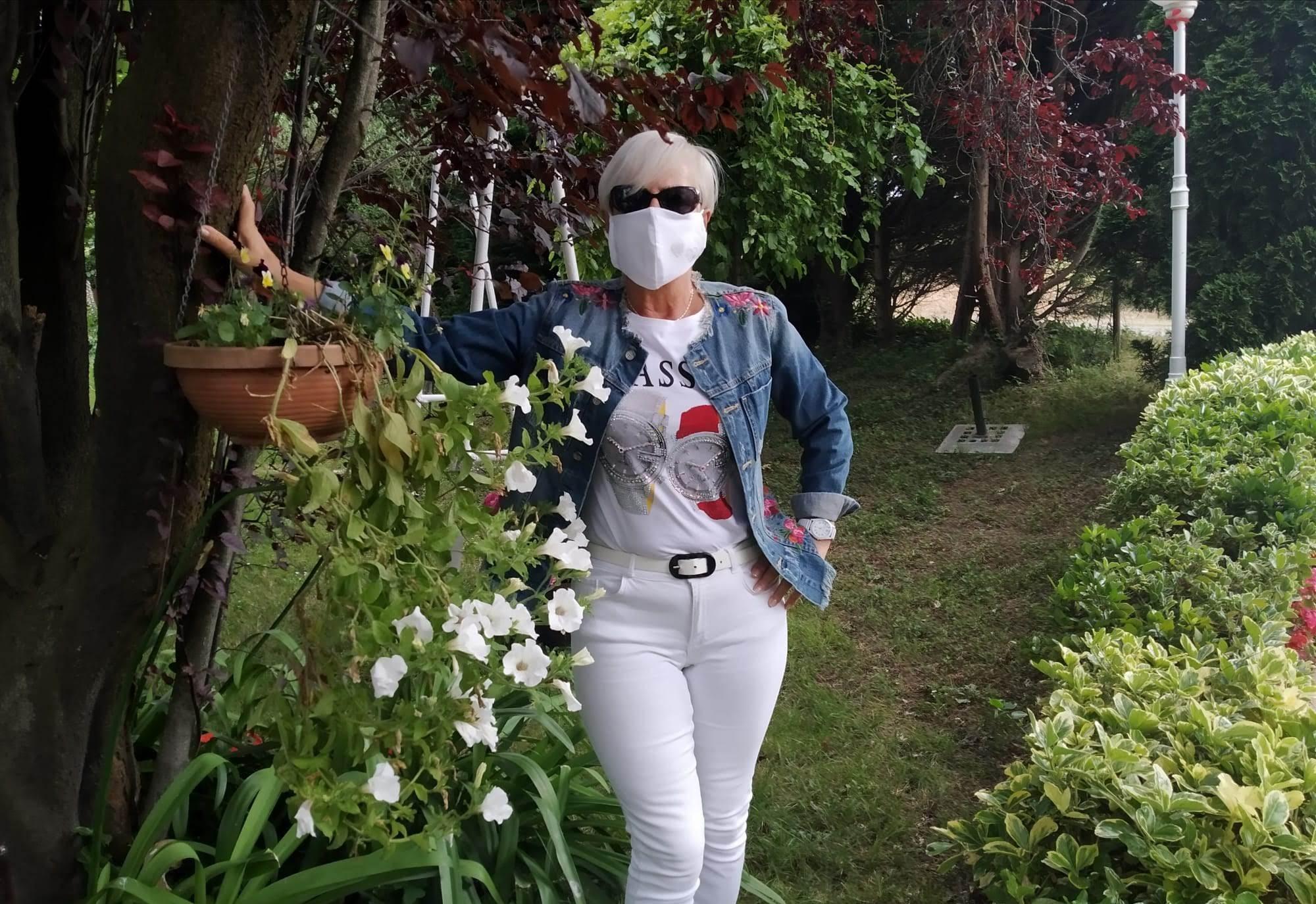 mi amiga Rosi con mascarilla entre flores y plantas