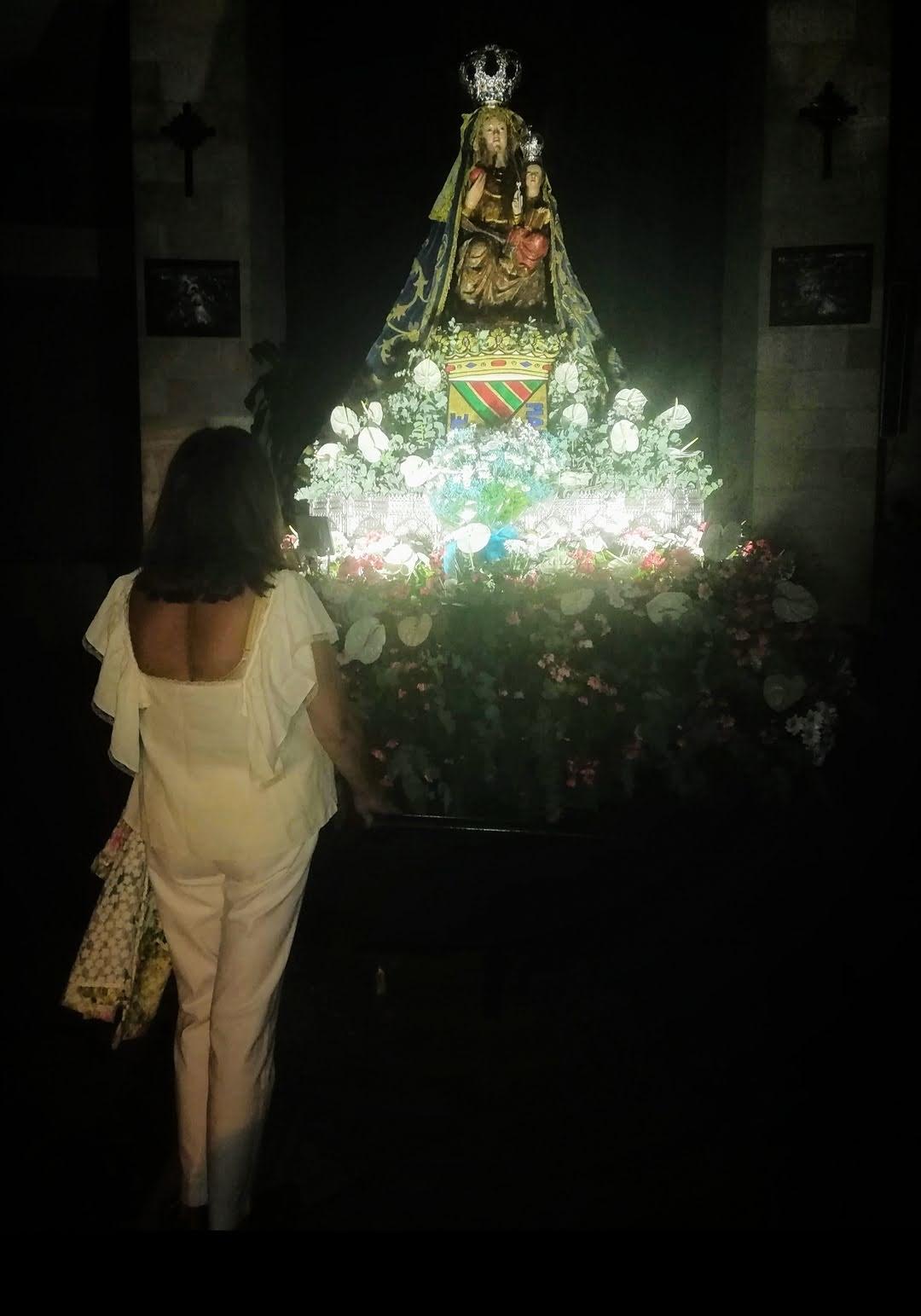 La abuela reza ante la figura de la virgen de su ciudad