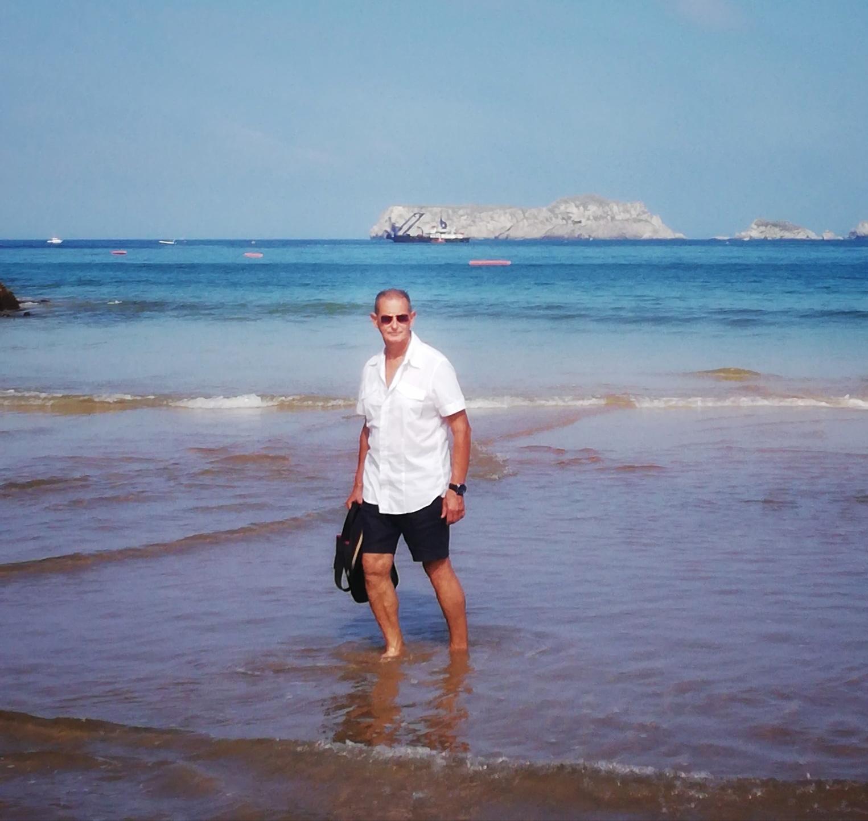 el abuelo pasea por el borde del mar.