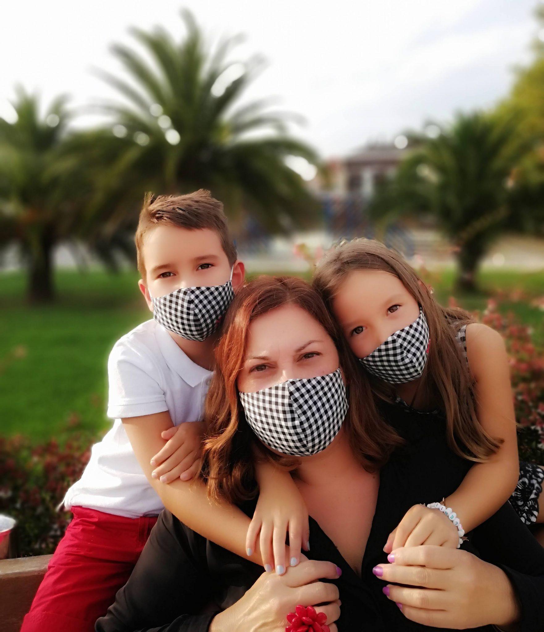 abuela a la ultima con sus nietos todos con mascarilla