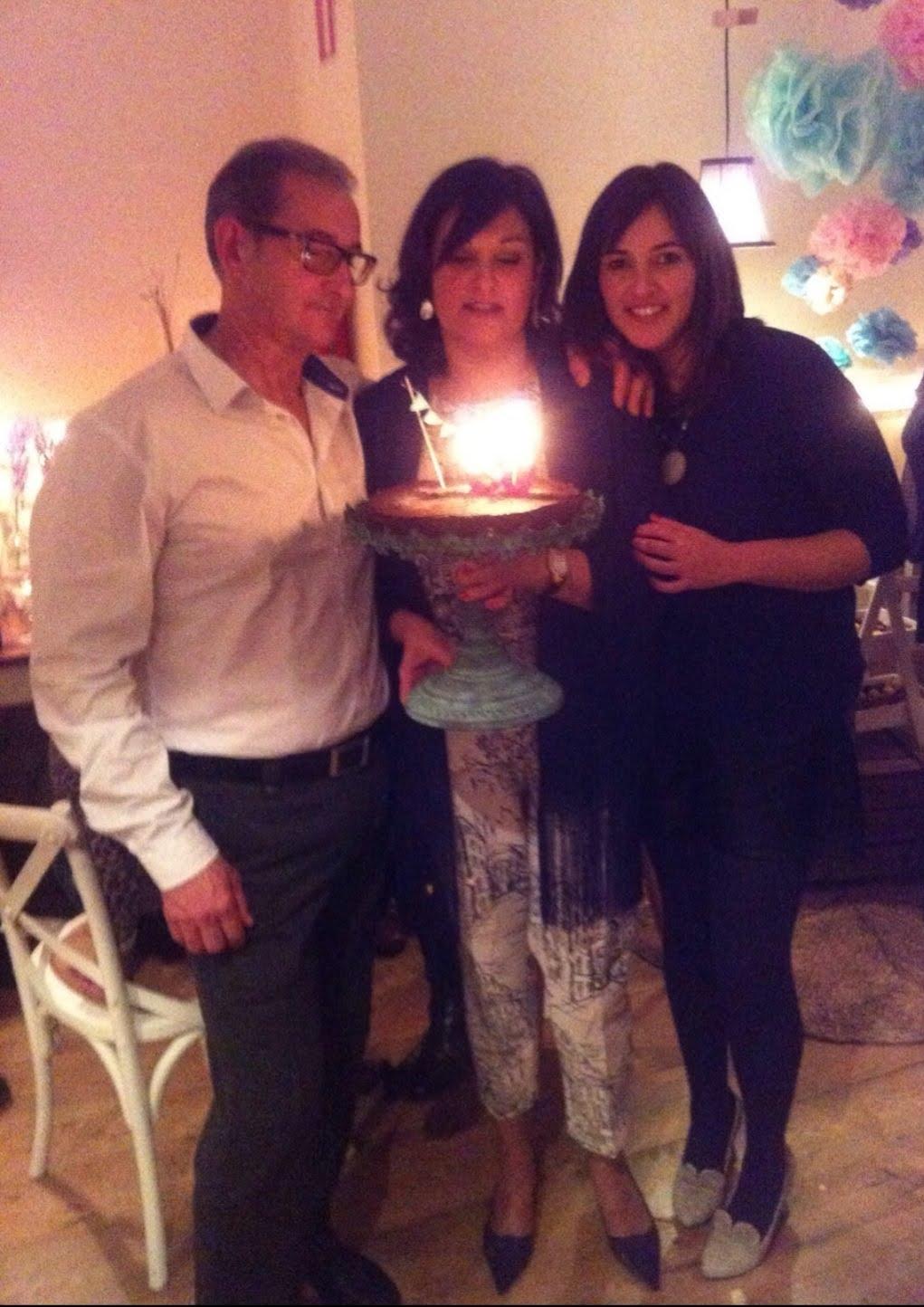 abuiela a la ultima con su marido y su hija soplando las velas de su cumpleaños