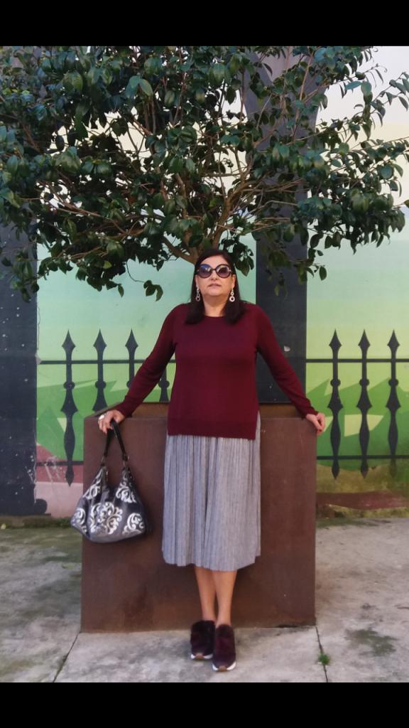 la abuela Maribel con ropa comoda y deportivas posando para foto delante de un macetero